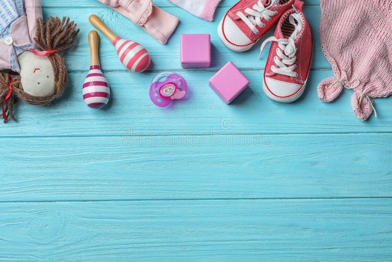 与婴孩辅助部件和玩具的平的被放置的构成在颜色木背景 免版税库存图片
