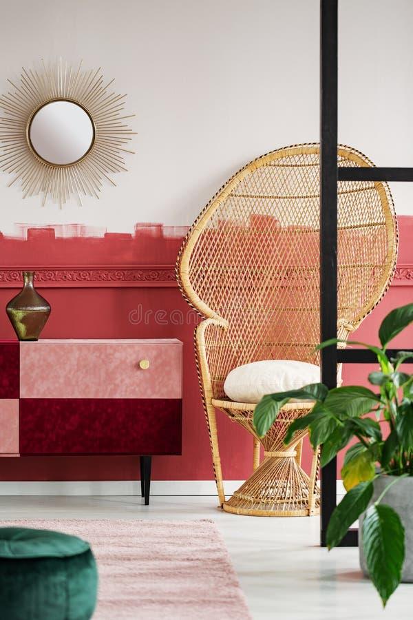 与孔雀椅子和手工制造粉红彩笔的时髦客厅内部和伯根地五斗橱 免版税图库摄影