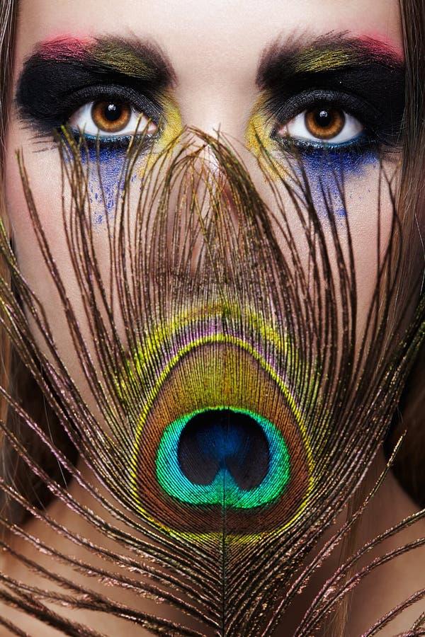 与孔雀羽毛的女性画象在前景和秀丽面孔构成 免版税库存照片