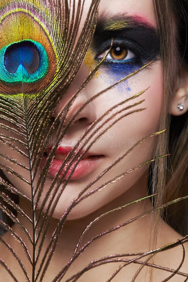 与孔雀羽毛的女性画象在前景和秀丽面孔构成 库存照片
