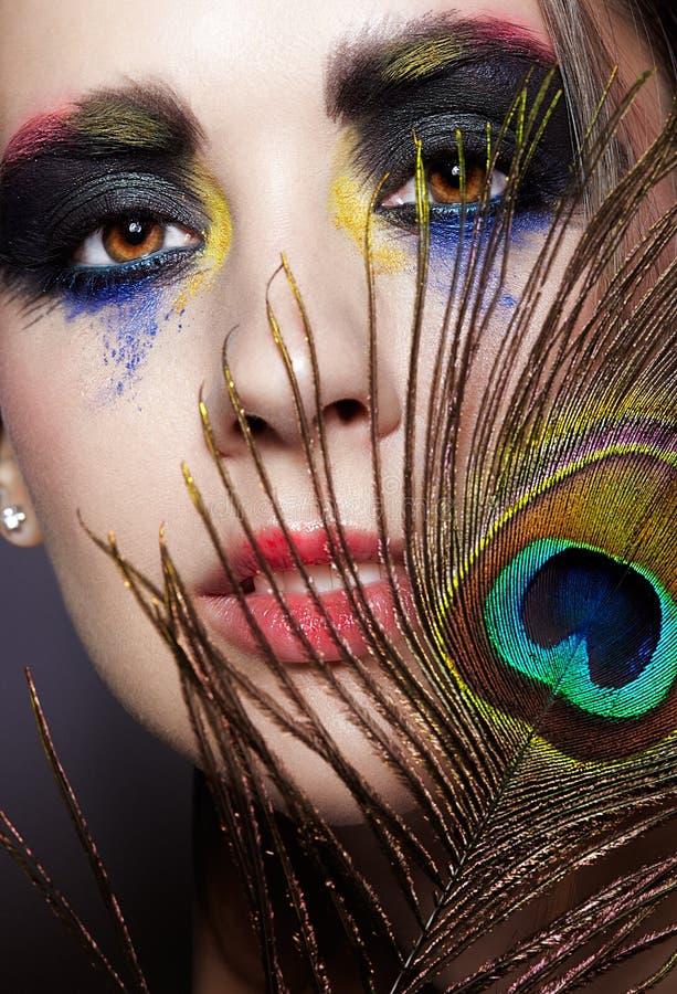 与孔雀羽毛的女性画象在前景和秀丽面孔构成 库存图片