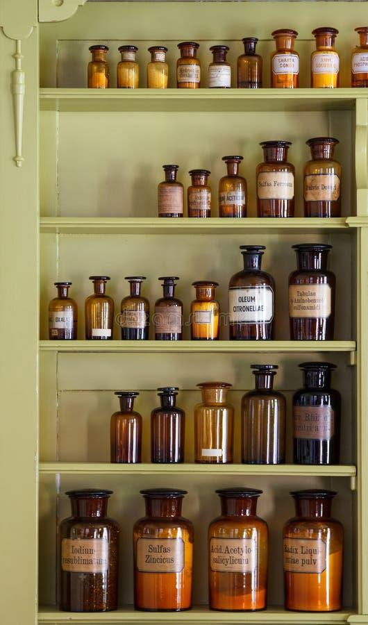 与存贮瓶子的老药商机柜 免版税图库摄影