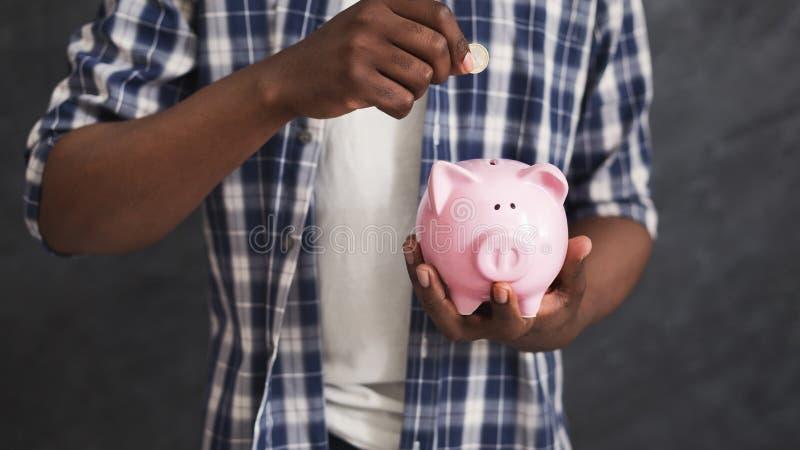 与存钱罐的黑人挽救 库存图片