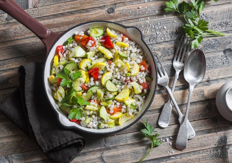 与季节性庭院菜的大麦米在木背景,顶视图的平底锅 夏南瓜、甜椒、南瓜和大麦炖 免版税库存图片