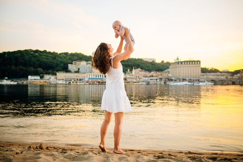 与孩子反目为仇日落和水的母亲 愉快的妈妈和婴孩 使用在海滩 扔她的儿子的年轻女人 免版税库存照片