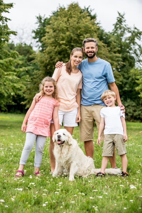 与孩子和狗的愉快的家庭 库存照片