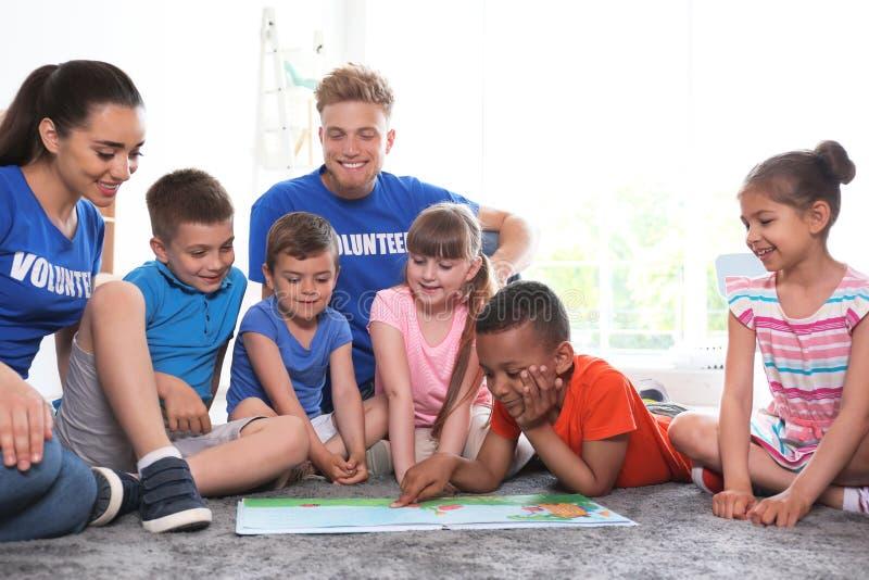 与孩子的年轻志愿者看书在地板上 图库摄影