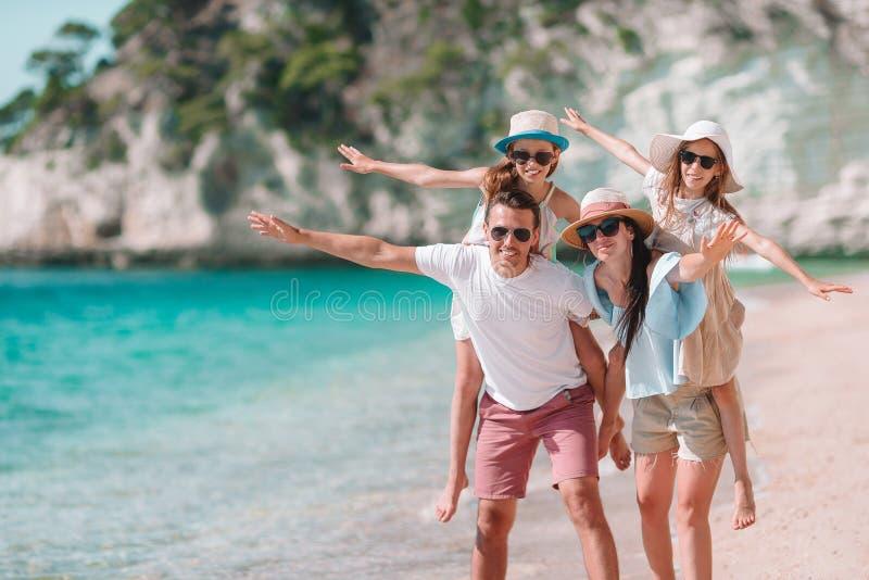 与孩子的愉快的美丽的家庭在海滩 库存图片