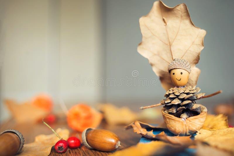 与孩子的秋天工艺 有人的儿童` s逗人喜爱的小船由自然材料制成 库存图片