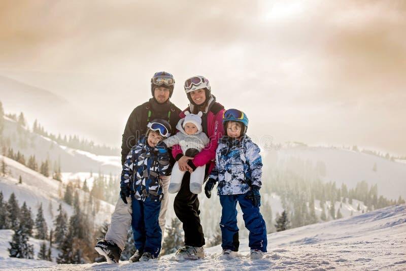 与孩子的美丽的家庭,滑雪在奥地利人的一个风景区域 免版税库存图片