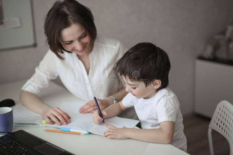 与孩子的美好的妇女家庭教师研究在家 免版税库存照片
