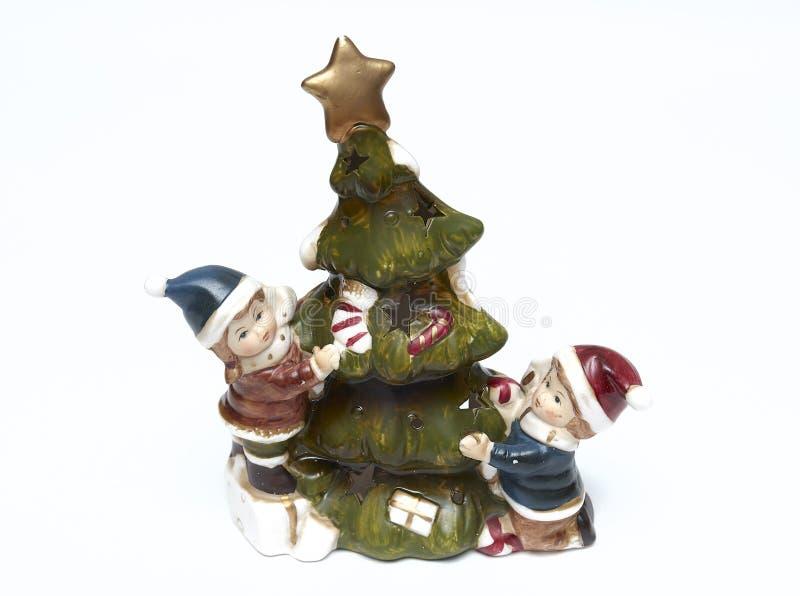 与孩子的陶瓷圣诞节小雕象绿色圣诞树白色背景的 孤立 库存照片