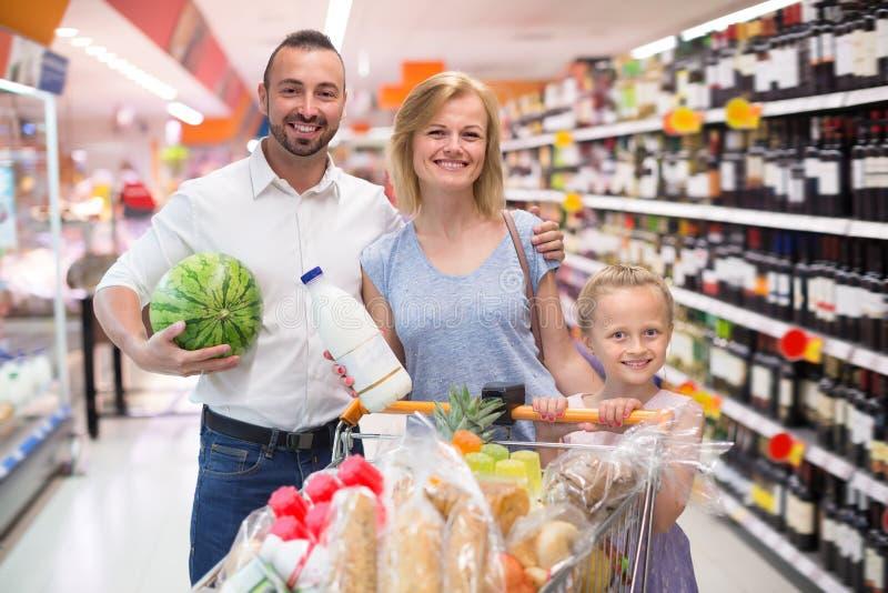 与孩子购物的成人家庭在大型超级市场 免版税库存图片