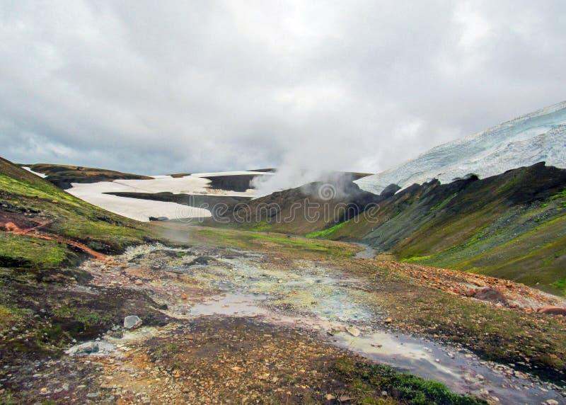 与它通入蒸汽的温泉城和五颜六色的流纹岩山,Laugavegur艰苦跋涉,冰岛的兰德曼纳劳卡地热地区 库存照片