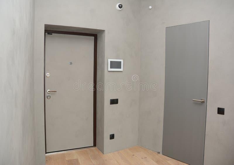 与安全CCTV照相机的现代房子入口金属门内部在有手动火警系统的室墙壁登上 免版税库存照片