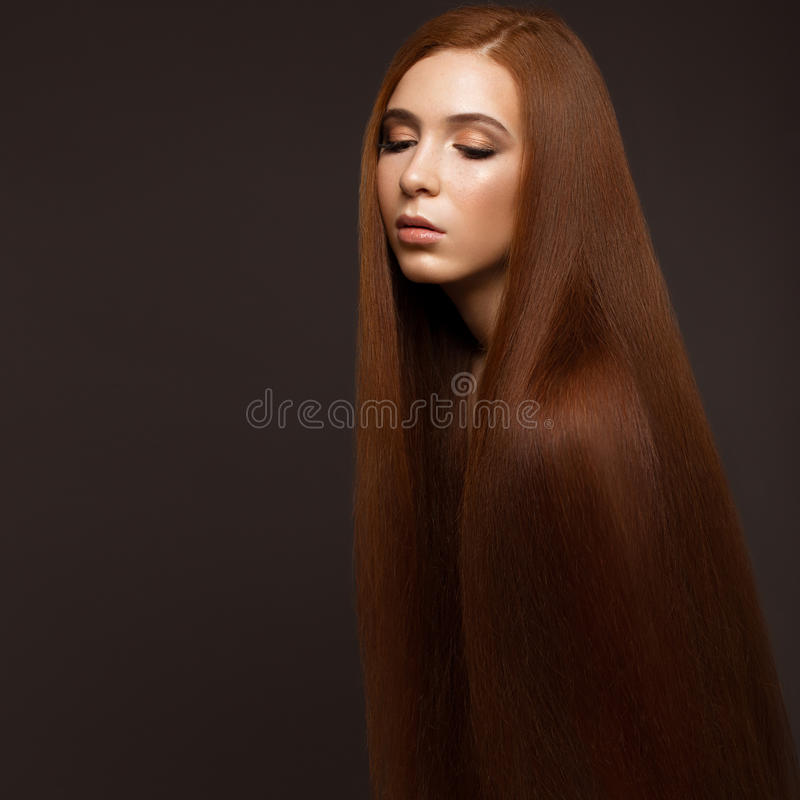 与完全光滑的头发和经典构成的美丽的Redheadgirl 秀丽表面 免版税库存图片