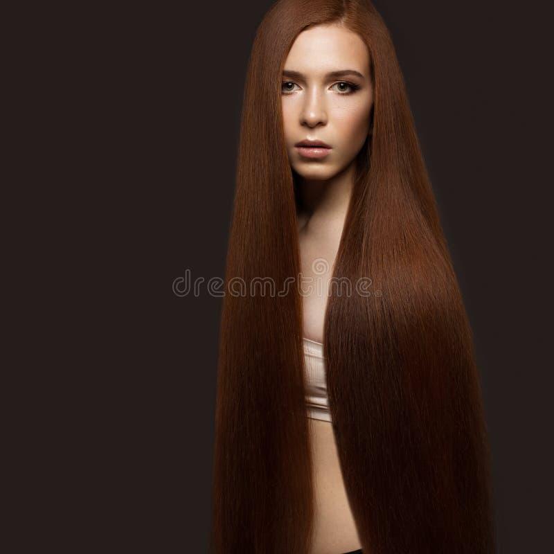 与完全光滑的头发和经典构成的美丽的Redheadgirl 秀丽表面 库存图片