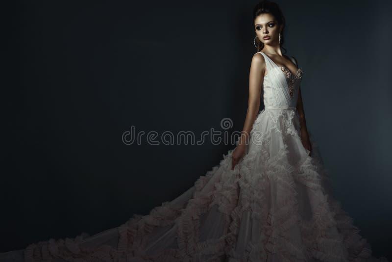 与完善的美好的年轻模型组成和并且刮了穿豪华蓬松婚纱的头发 免版税库存图片