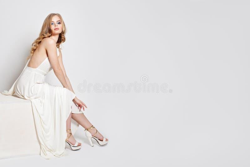 与完善的腿的美好的模型在高跟鞋鞋子 白色礼服的妇女 白色背景的俏丽的妇女 库存照片