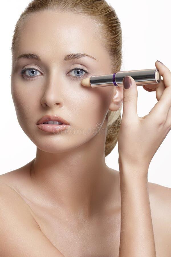 与完善的被定调子的皮肤的美好的少妇模型 concealer 免版税库存图片