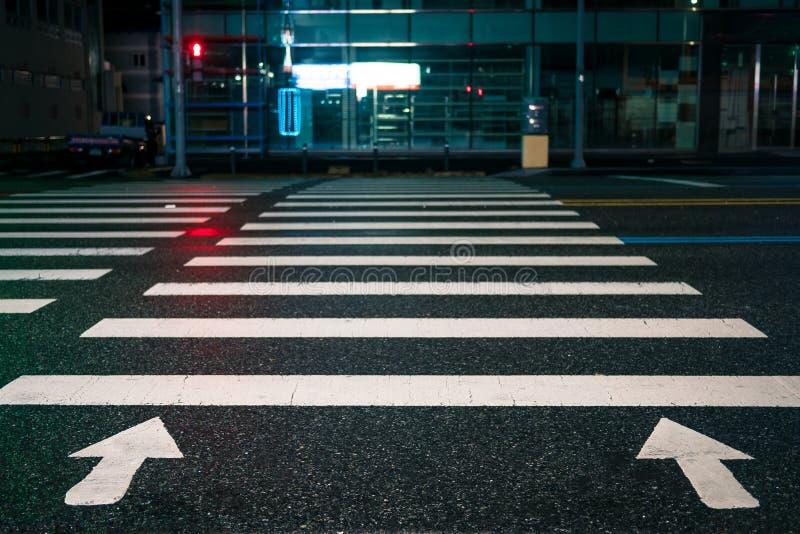 与定向箭头的行人交叉路在晚上 库存照片