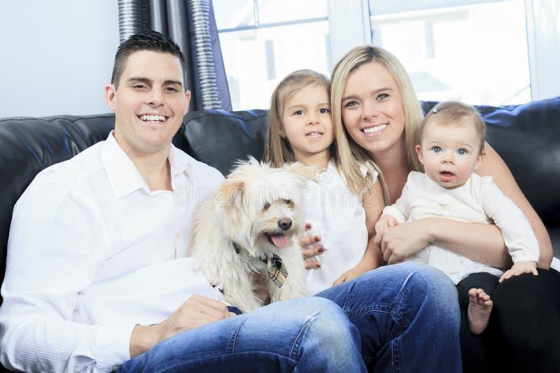与宠物的家庭在家坐沙发 免版税库存照片