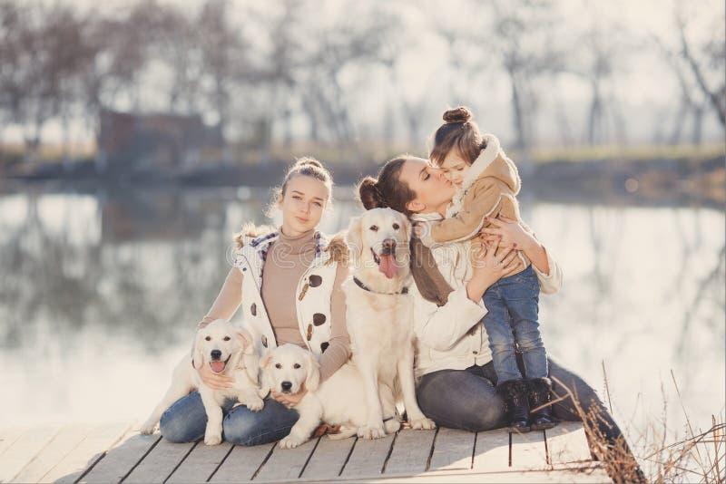 与宠物的愉快的家庭在湖附近 免版税库存照片