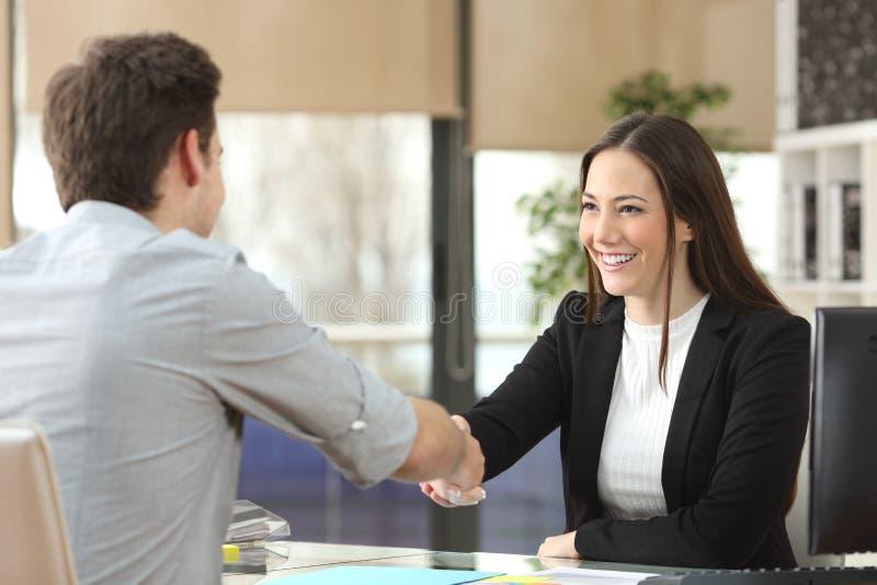 与客户结束成交的女实业家握手 免版税图库摄影