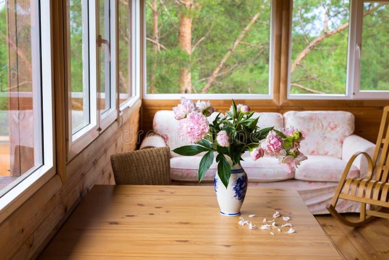 与家具的一个舒适大阳台有俯视森林-沙发,在一个花瓶的牡丹的全景窗口的在桌上和 库存图片