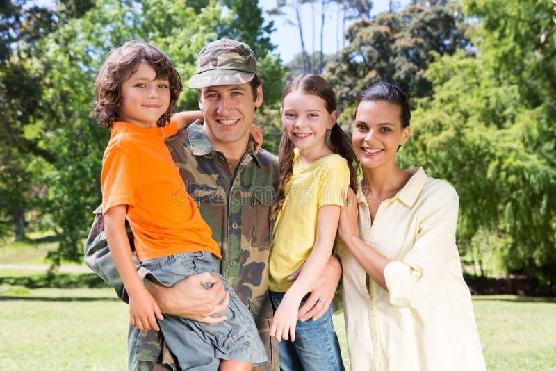 与家庭团聚的英俊的战士 库存照片