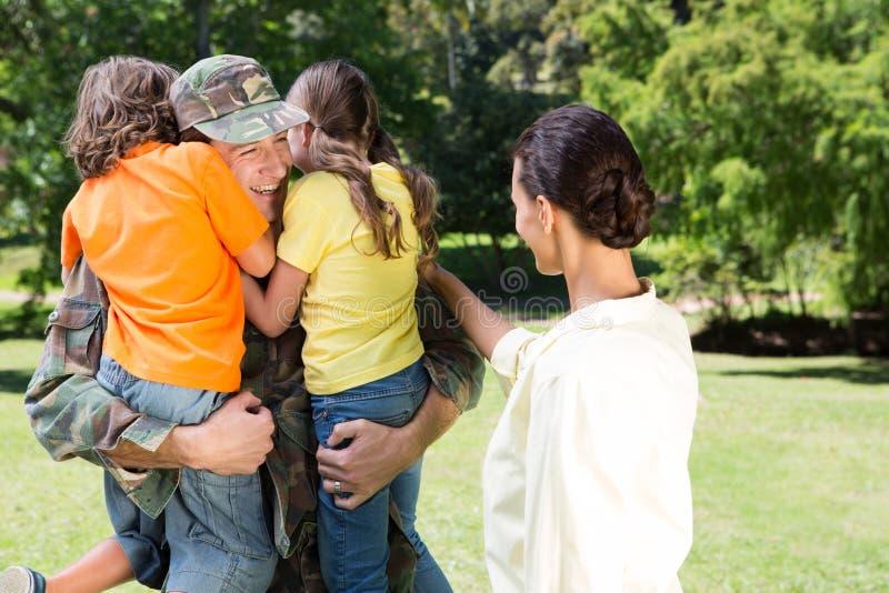 与家庭团聚的英俊的战士 免版税库存照片