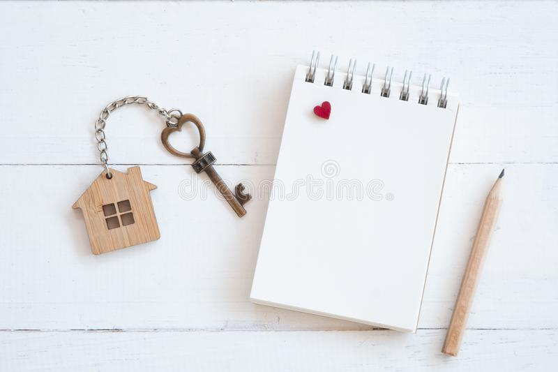 与家庭钥匙圈、空白的笔记本和铅笔的议院钥匙在白色木桌背景 库存照片