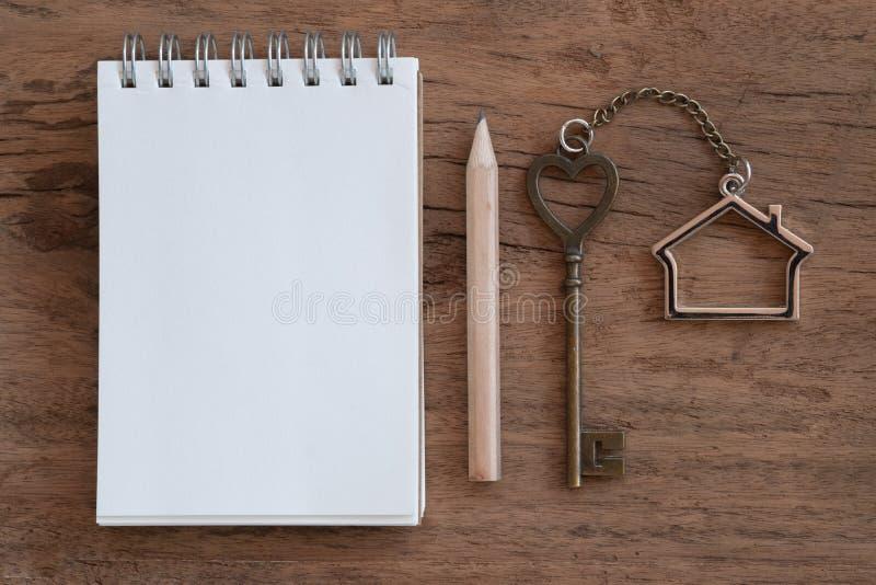 与家庭钥匙圈、空白的笔记本和铅笔的议院钥匙在老木桌背景 库存照片