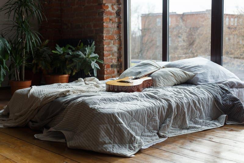 与宽床在窗口附近,顶楼样式的舒适的卧室内部 与绿色植物的现代内部 在床上的吉他 免版税库存照片