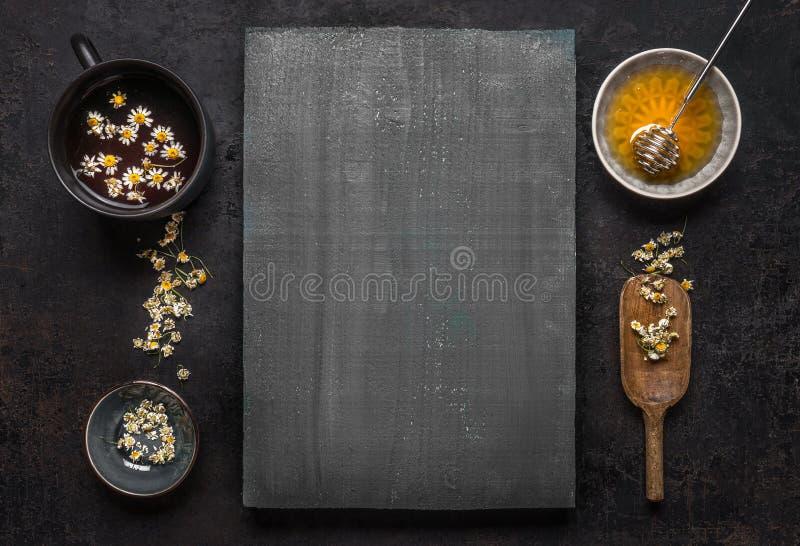 与宽松干春黄菊花、杯子清凉茶和蜂蜜的草药背景与在木,顶视图的匙子 免版税库存图片