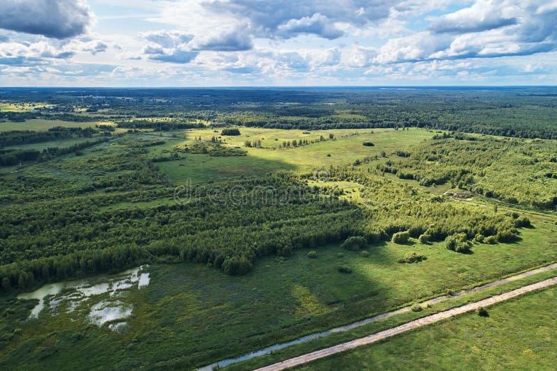 与寄生虫的航拍 与绿色森林、路和河的风景 免版税库存照片