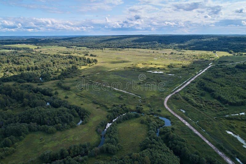 与寄生虫的航拍 与绿色森林、路和河的风景 库存图片