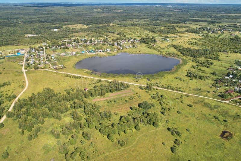 与寄生虫的航拍 有绿色森林、路和湖的村庄 免版税库存图片