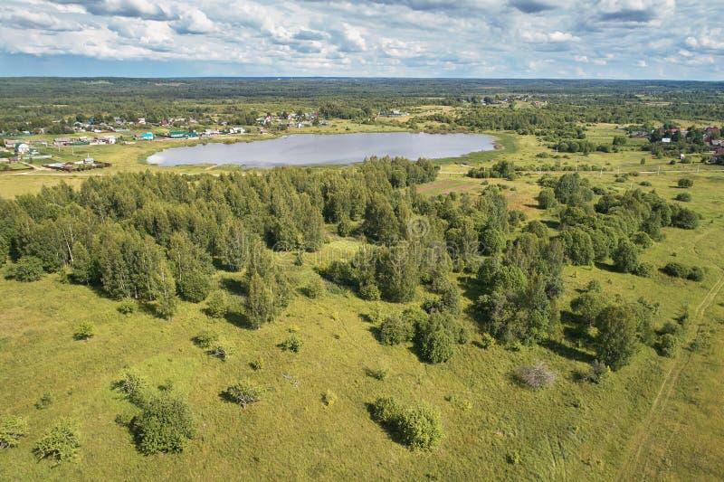 与寄生虫的航拍 有绿色森林、路和湖的村庄 库存照片