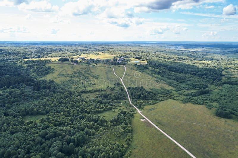 与寄生虫的航拍 有绿色森林、路和领域的村庄 图库摄影