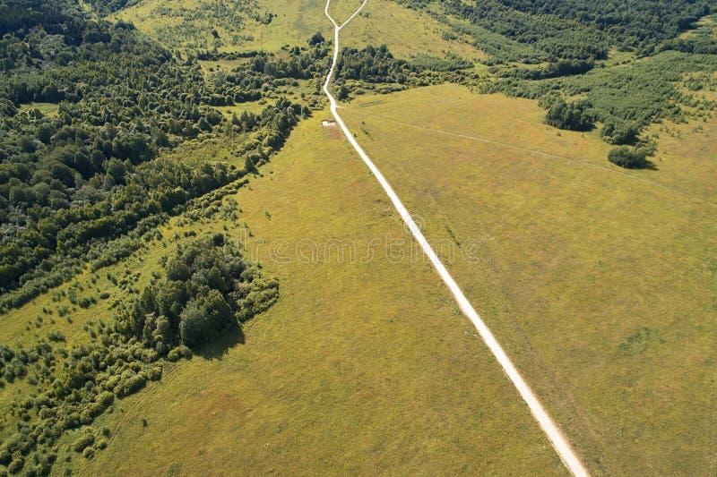 与寄生虫的航拍 运行通过领域和森林的平直的土路 库存照片