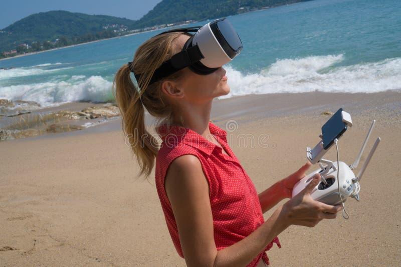 与寄生虫采取照片和录影在海滩的照相机和虚拟现实玻璃的Woan 免版税图库摄影