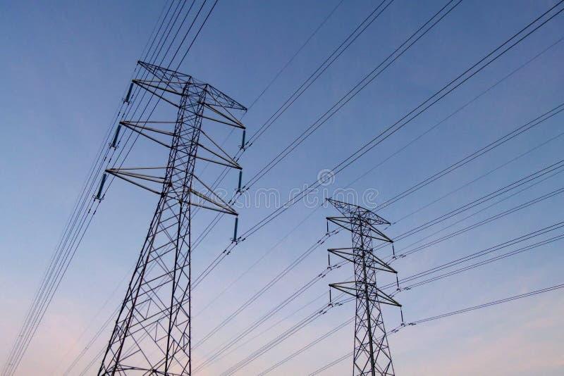 与导线的电塔在黑剪影在清早,放大 免版税库存图片