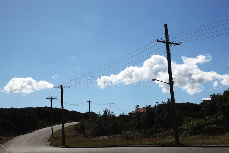 与导线的电线杆在一条空的街道上 免版税图库摄影