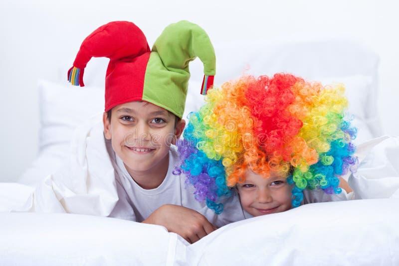 与小丑帽子和头发的愉快的孩子 免版税库存照片