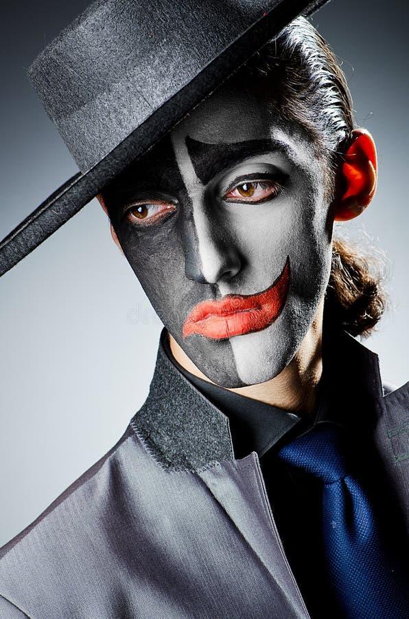 与小丑油漆的生意人 库存照片