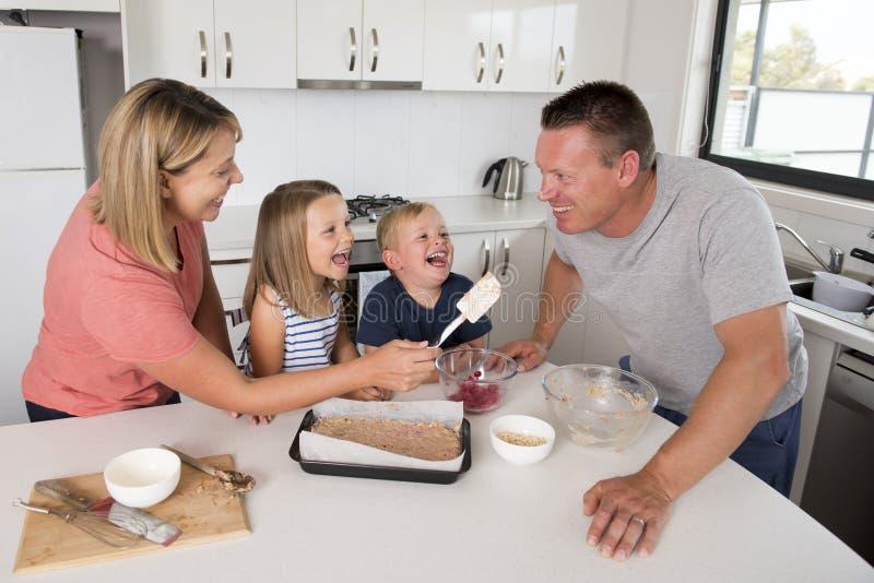 与小儿子和年轻美丽的获得女儿在家的厨房一起的年轻愉快的夫妇烘烤使用与奶油的乐趣 免版税库存图片