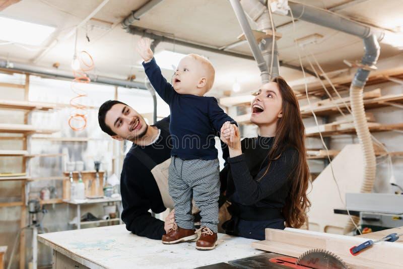 与小儿子的愉快的年轻家庭在木匠车间 免版税图库摄影