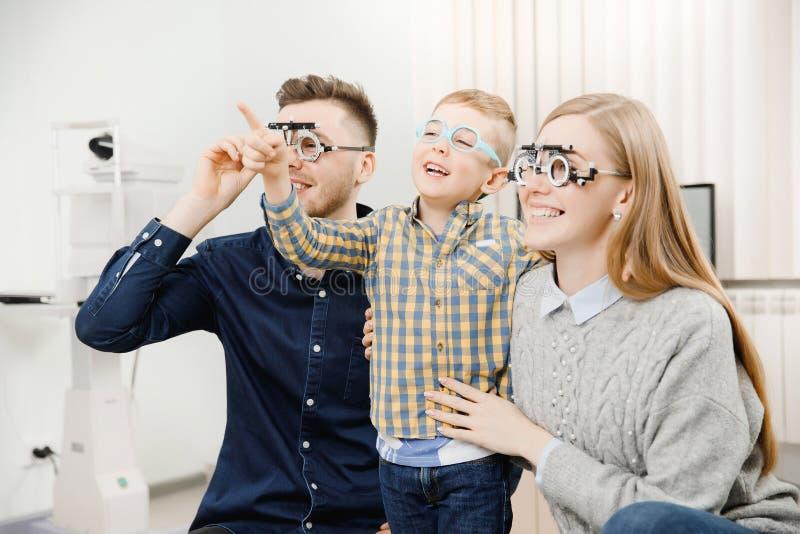 与小儿童招待会医生眼科医生的快乐的家庭使用玻璃 免版税库存图片