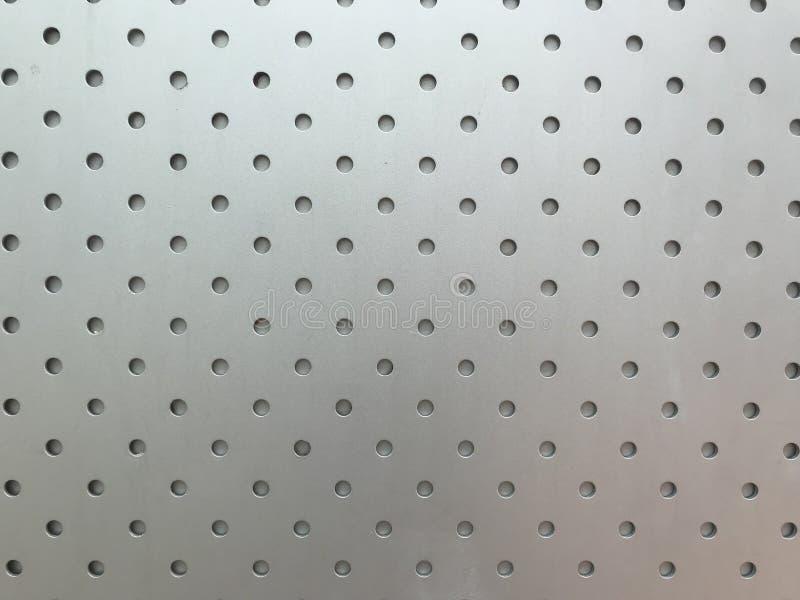 与小圈子孔的银色金属板表面 免版税库存图片